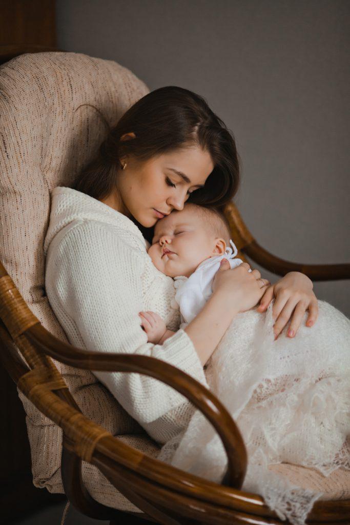 Bebê dormindo no colo de sua mãe